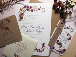 A wedding invitation set in a rustic blackberry design