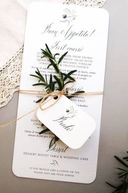 An italian wedding place name card and menu with a sprig of rosemary tied in a bundle