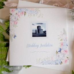 a wedding invitation with a summer floral display