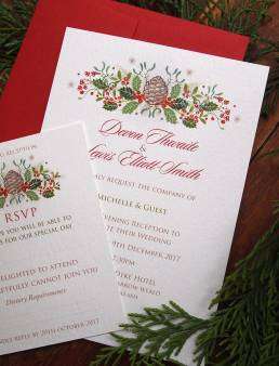 Christmas wedding invitations and RSVP in a festive holly and pine cone design