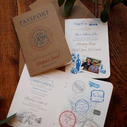 A passport style wedding invitation booklet with travel graphics