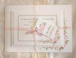 A floral wedding invitation set with a pink rose design all tied together with a pink ribbon and a tag with the bride and grooms names
