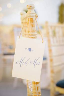 A place name card hung on the back of a chair at the wedding reception
