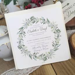 A rustic wedding invitation with a spring wreath design
