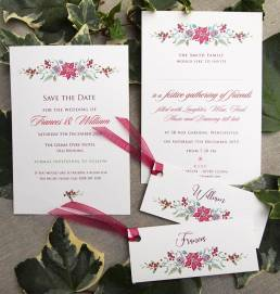 Winter wedding stationery set with a red and green poinsettia design